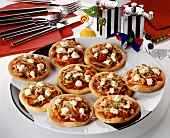 Mini-pizzas with vegetables & sheep's cheese as party snacks