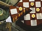 Chess board cake with marzipan crowns, a piece cut