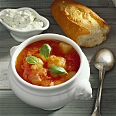 Tomato soup with vegetables, baguette & herb quark in bowl