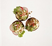 Canapes with matje herring tartare, radish slices & cress