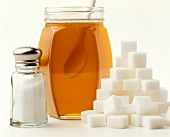 Sugar lumps, honey in jar and icing sugar in sifter