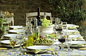 Laid table with olives, oil & wine as table décor (outdoors)