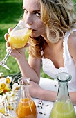 Young woman drinking healthy juices (outdoors)