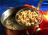 Millet noodles (Spaetzle) on ladle above pan