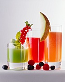 Three different fruit juices in glasses, fruit & berries