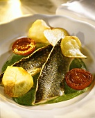 Brook trout fillet on green sauce with potato crisps & tomatoes
