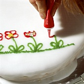 Decorating a cake with flowers (icing from a tube)