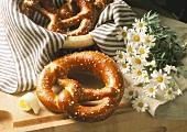Salt pretzels on wooden board & in bread basket; marguerites