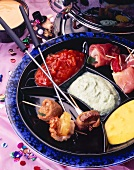 New Year's Eve fondue with stuffed skewered meat & sauces