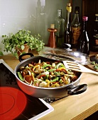 Colourful vegetable stir-fry on trivet next to the oven