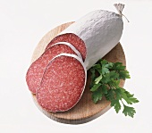 Salami, two slices cut, with parsley on board