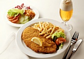 Breaded escalope with chips, salad plate, glass of beer