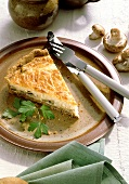 A piece of savoury mushroom &  cheese quiche on plate