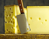 Two pieces of Emmental on wooden board with cheese knife