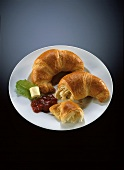 Two croissants on plate with berry jam and butter