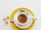weiße Tasse Kaffee mit weißem Unterteller auf gelben Teller