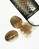 Two nutmegs, one partly grated and a grater