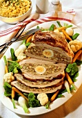 Stuffed veal breast with boiled egg and bowl of noodles