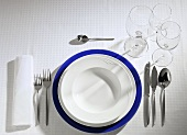 Table setting: blue, white & soup plate, cutlery, wine glasses