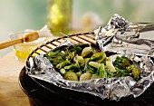 Vegetable parcel (foil with mixed green vegetables) on barbecue