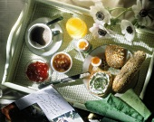 Breakfast tray with wholemeal pastry, egg, jam and coffee