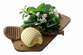 Butter curl on wooden board with herb bouquet