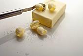 Butterroller zieht Butterröllchen vom Butterstück