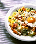 Fried egg on sliced potatoes with bacon, carrots, cream sauce