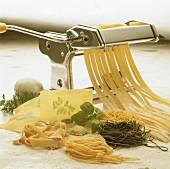 Still life: pasta dough in pasta machine, various pastas