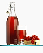 Redcurrant juice in bottle & glass & fresh redcurrants