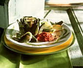 Boiled artichoke with tomato dip on plate