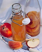 Apple Vinegar in a Glass Bottle with Fresh Apples