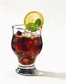 A glass of Cola with ice, decorated with mint & lemon slice