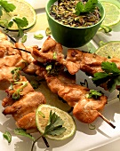 Chicken kebabs, lime slices, and bowl of marinade