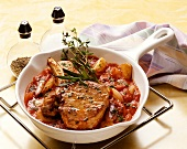 Veal cutlet on tomato sauce in white china pan