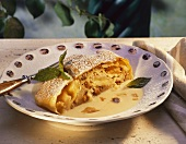 A piece of apple strudel with custard on plate