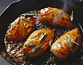 Frying chicken breasts with sage in frying pan