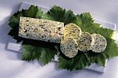 Eine Rolle Kräuterbutter, angeschnitten, auf Weinblättern