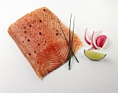 Piece of salmon with pepper, garnished with chives, onions