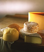 Various types of cheese on wooden platter & cheesecloth