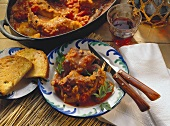 Braised rabbit in tomato sauce on plate & in cooking dish