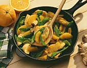 Turkey and orange ragout with mangetouts in pan