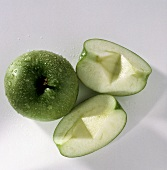 Whole Granny Smith Apple with Two Apple Wedges; Water Drops