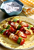 Colourful fruit kebabs on plate & a bowl of fruit quark