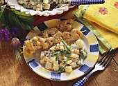 Potato salad with vegetables on plate with two poultry kebabs