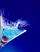 Blauer Curacao-Cocktail schwappt aus Martiniglas