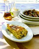A piece of potato tortilla & plate of fried mushrooms