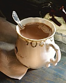 Cocoa in a bulbous china cup with spoon