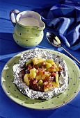 Exotic fruits baked in aluminium foil with vanilla sauce