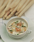 A plate of white asparagus cream soup with chervil & croutons